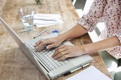 Woman using laptop at dining room table