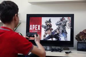 A man plays PlayStation 4 on an older TV.
