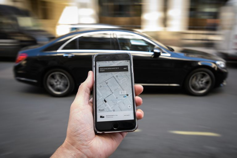 Hand holding Uber app in front of a car