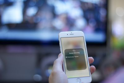 Someone starting a screen mirroring from an iPhone to a smart TV.