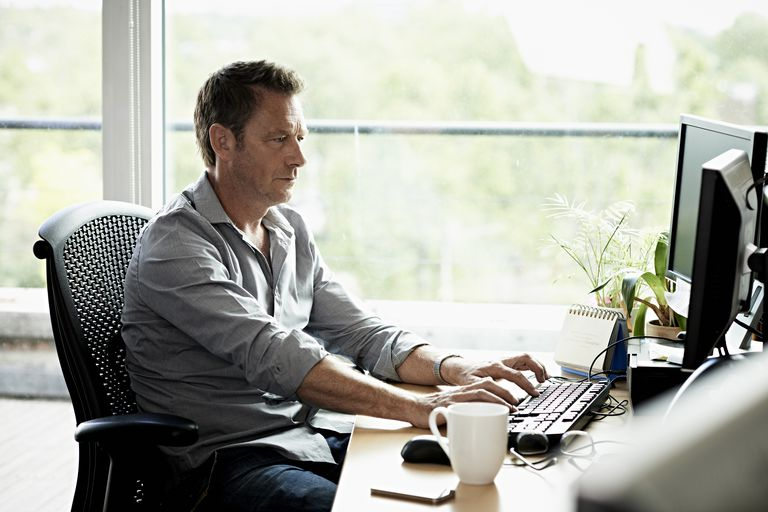 man using computer with multiple monitors at desk