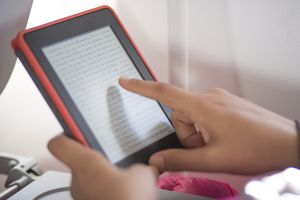 Hand pointing at screen using an e-reader