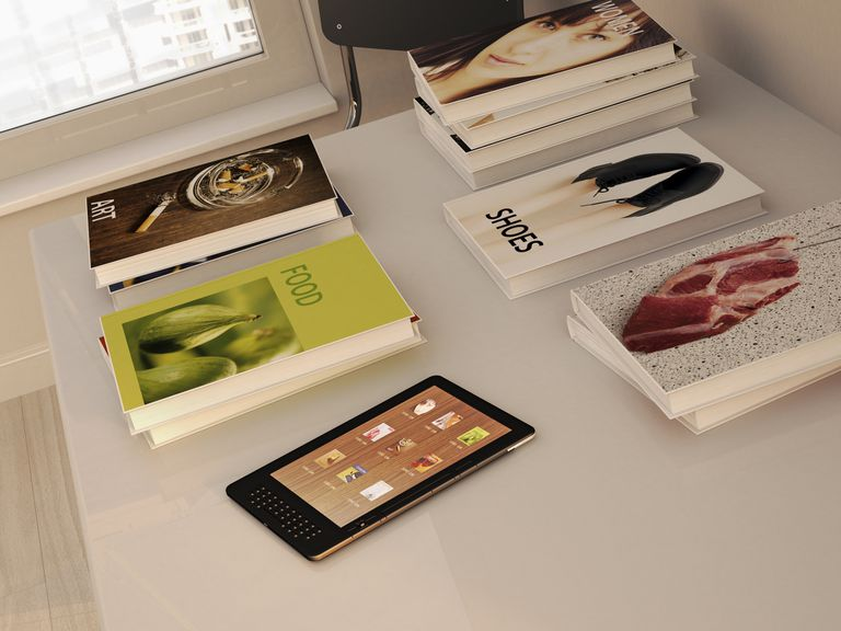 E-reader and books lying on a table