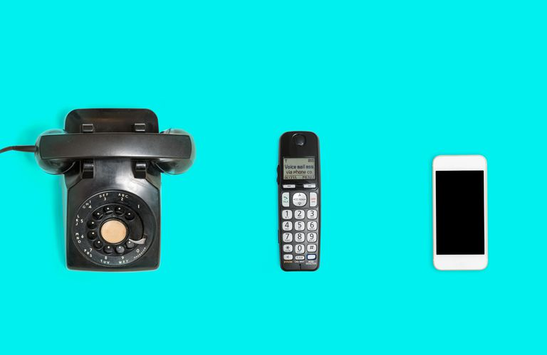 Landline phone, cordless phone, and mobile phone lined up next to each other