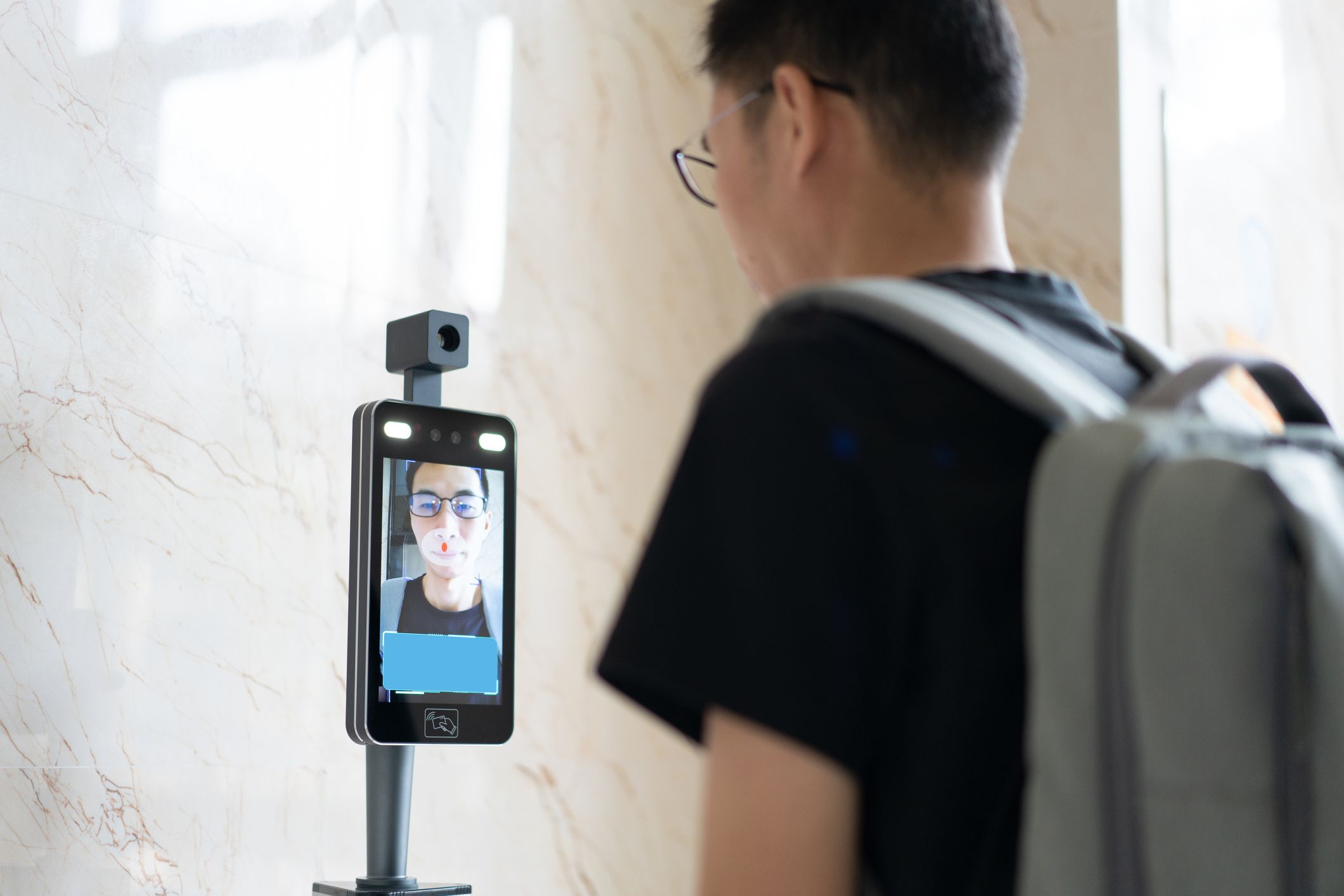 Person standing in front of a facial recognition system