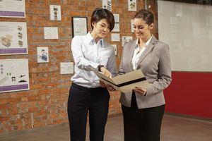 Worker showing female manager a print brochure