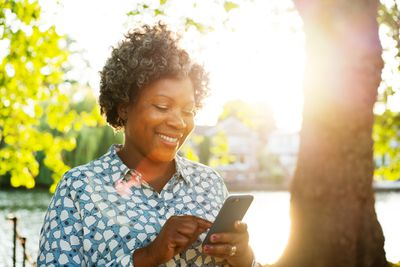 A woman sitting outside smiling at her smartphone
