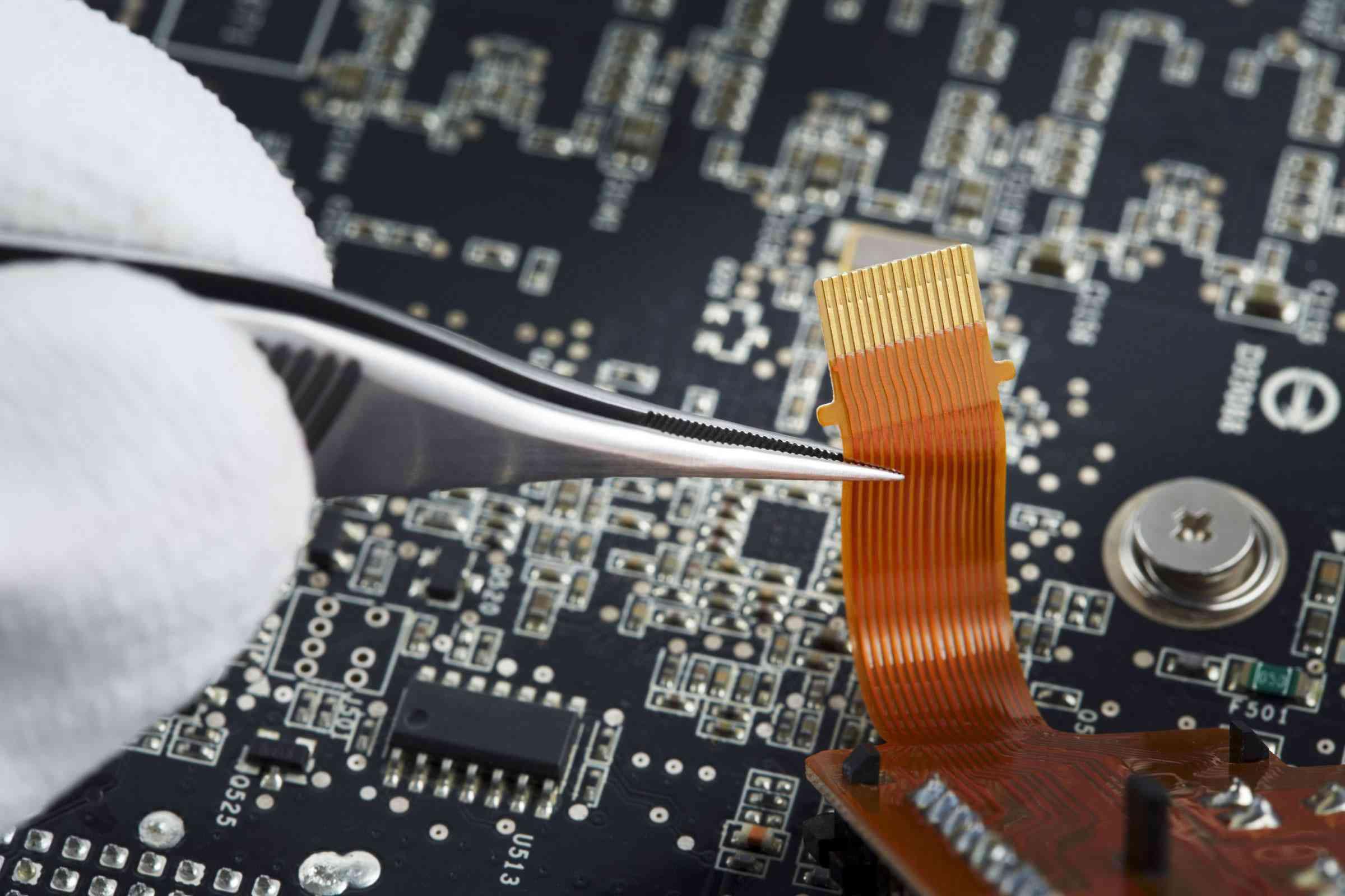 Human hand repairing printed circuit board, close up