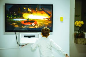 Boy playing video games in front of a flat screen TV