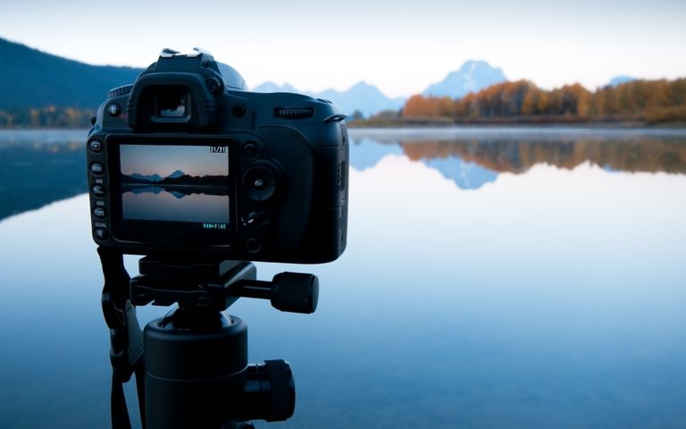 Camera on tripod capturing lakes and mountians