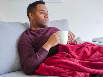 A person watching TV with a blanket and white coffee mug