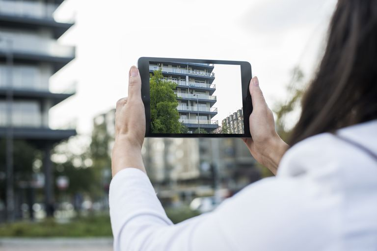 Woman taking a picture of a building with an iPad Mini