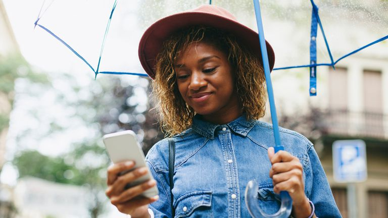 Woman standing in the rain with an umbrella checking her iPhone weather app