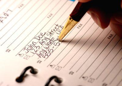 A pen writing in an address book