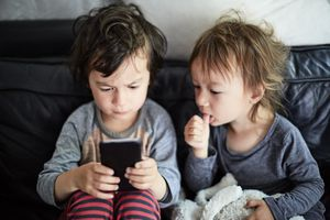 Two toddlers looking intently at a smartphone