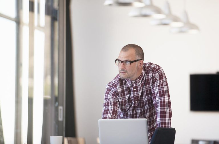 Man in plaid shirt at laptop, staring out window