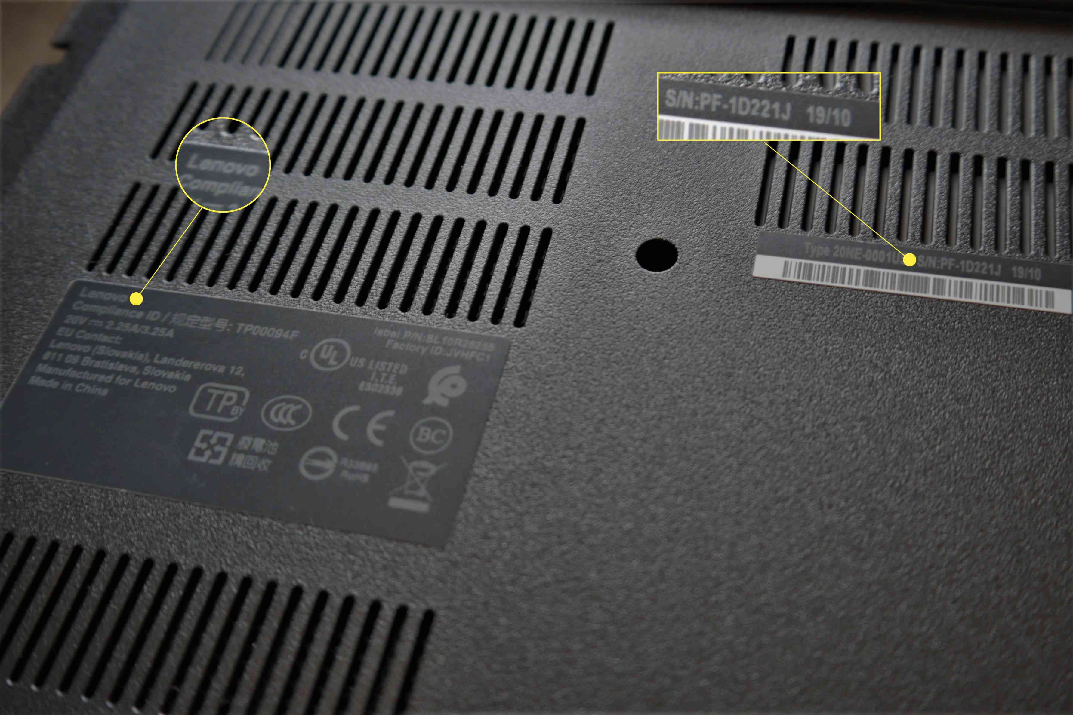 A photo of the bottom of a laptop with the serial number and manufacturer name highlighted.