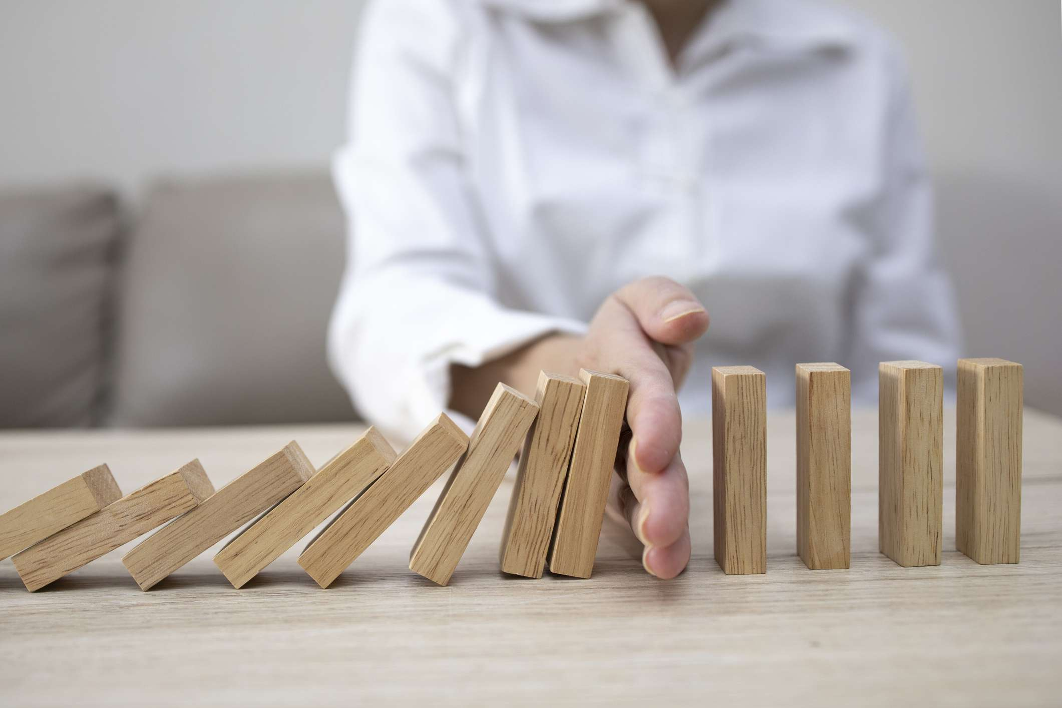 hand stopping wooden blocks from falling over