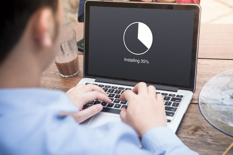 Young man waiting for installing update with circle load percentage waiting indicator concept using laptop