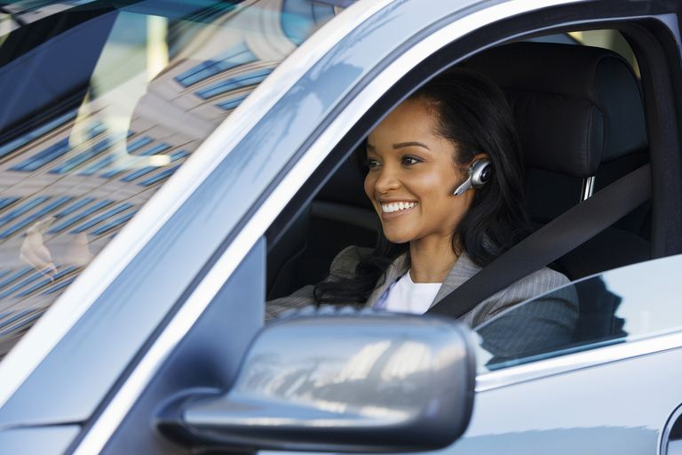 Businesswoman driving in car, using mobile phone hands-free device, smiling, side view