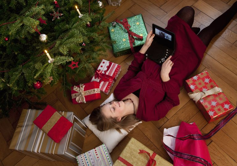Girl watching movie on DVD player under Christmas tree