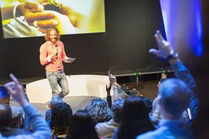 Speaker on stage answering audience questions during a presentation