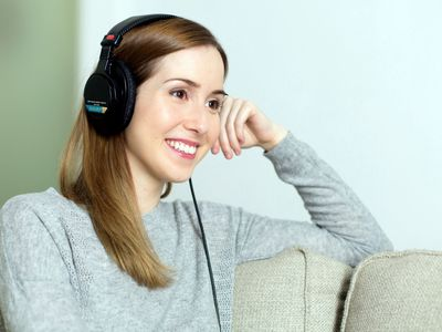Podcast listener smiling while listening to podcast through headphones.