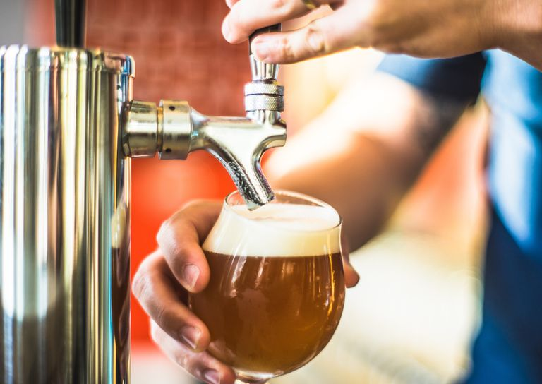 Close-Up Of Man Pouring Beer In Bar