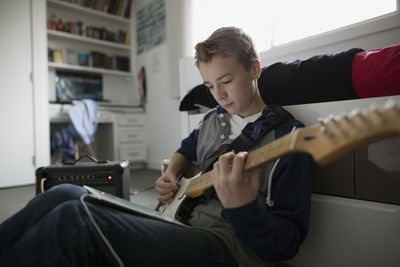 Boy playing guitar plugged into tablet