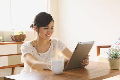 Young woman using a tablet to access her AIM mail