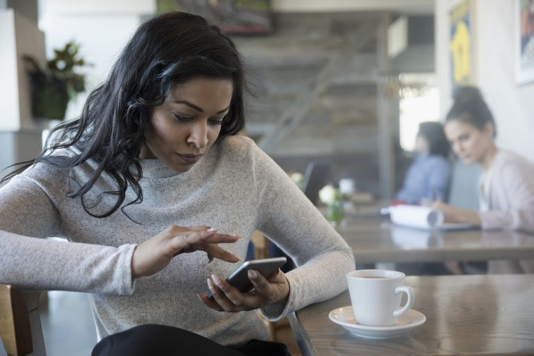 Woman using smart phone, drinking coffee in cafe