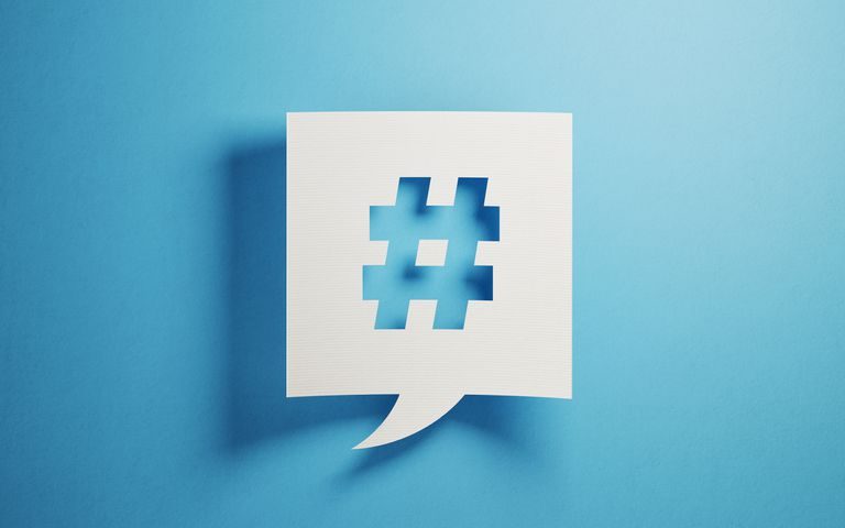 Cutout piece of paper with a speech bubble with a hashtag in it on a blue background