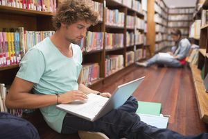 Student using laptop while sitting on floor in library
