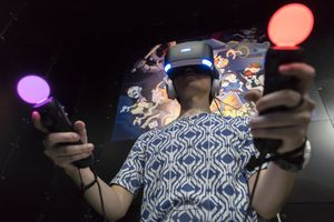 A person using a PlayStation VR headset with two Move controllers