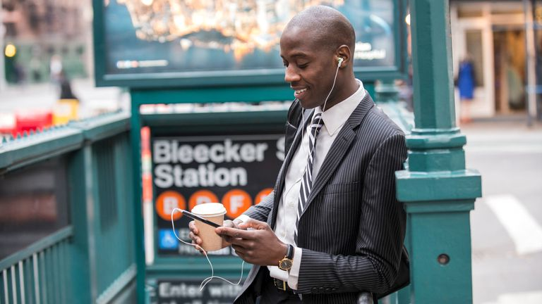 A businessman standing near the subway listing to a podcast on his smartphone.