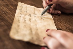 Close-Up Of Human Hand Holding Paper and writing in cursive