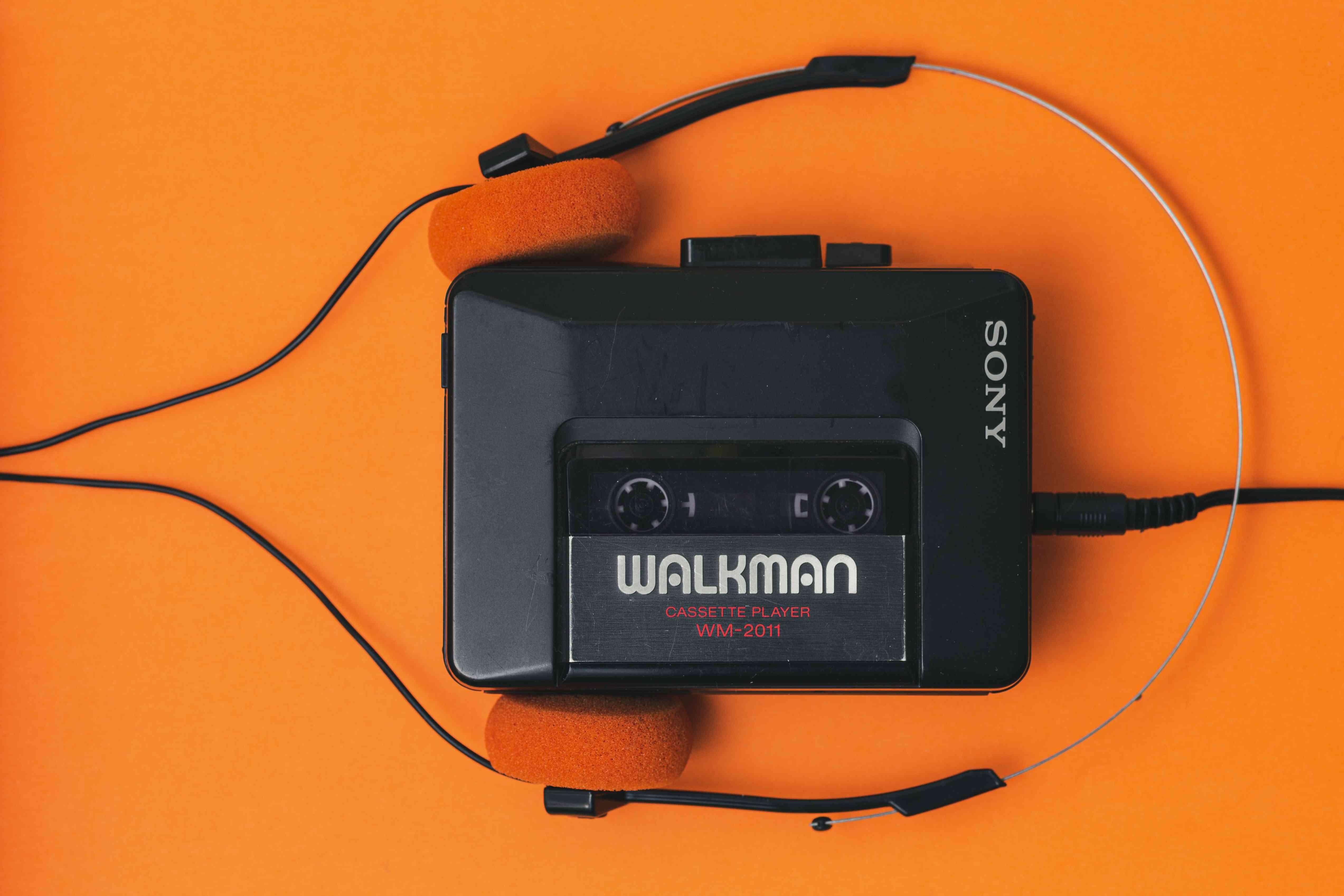 A Sony Walkman on an orange background.