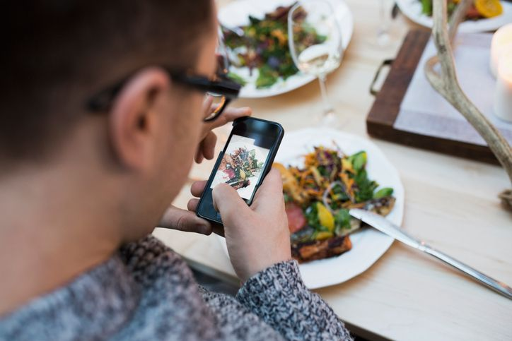 Man taking photo of food on iPhone