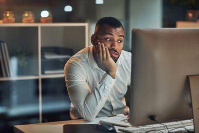 Bored man starting at computer screen