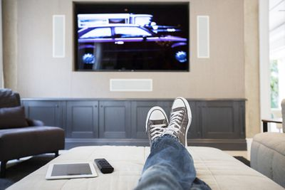 Feet with sneakers in front of flat-screen TV on a wall.