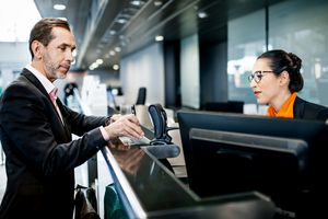 A businessman using a mobile boarding pass to check in at an airline desk in an airport.