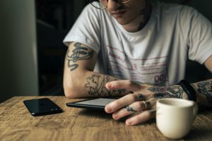 Someone reading on a Kindle e-book reader while having a coffee.