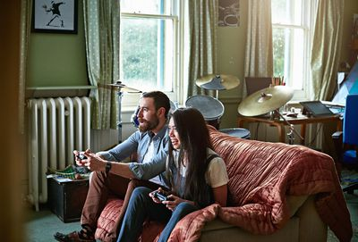 A man and woman sitting on a couch holding games controllers while smiling at an off-screen games console