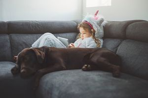 Young girl in a unicorn onesie using tablet, dog by her side
