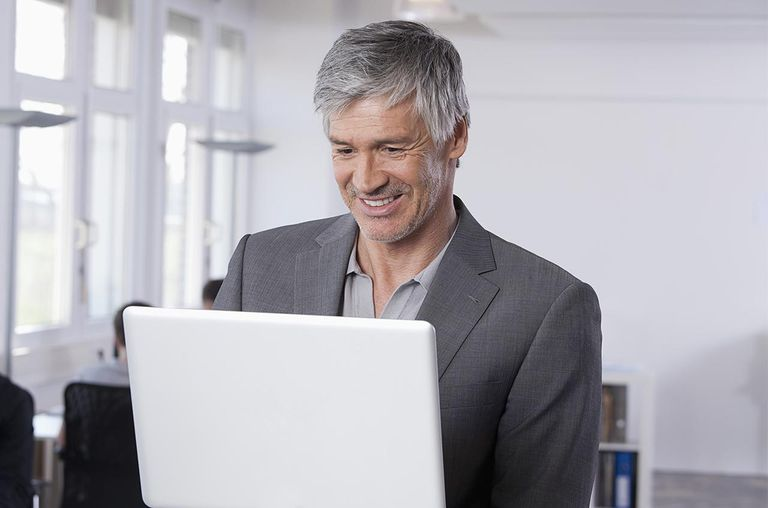 Mature man using laptop, colleagues working in background