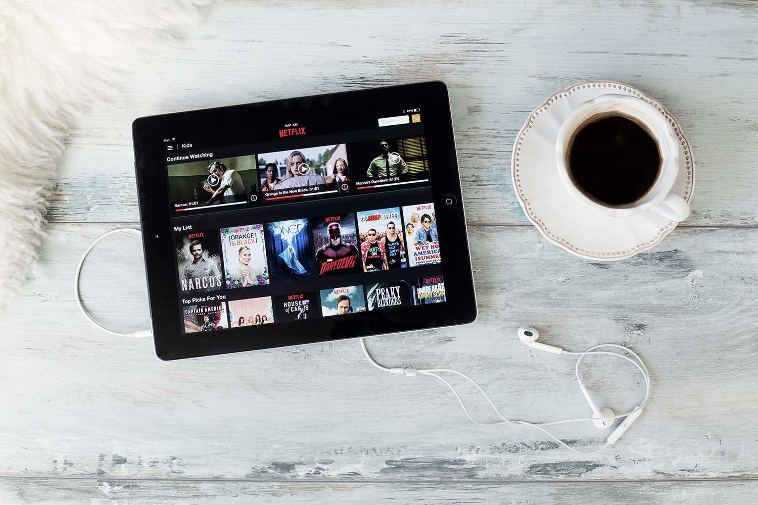 Netflix on iPad connected to Apple EarPods next to a cup and saucer of coffee on a wood floor