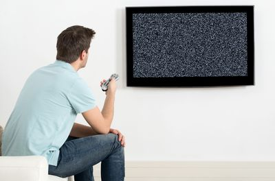 Man in blue shirt pointing a TV remote at a television with no signal.