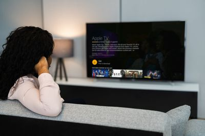 A woman installs Apple TV on a Fire Stick with a TV.