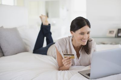 Online shopper on laptop with credit card in hand