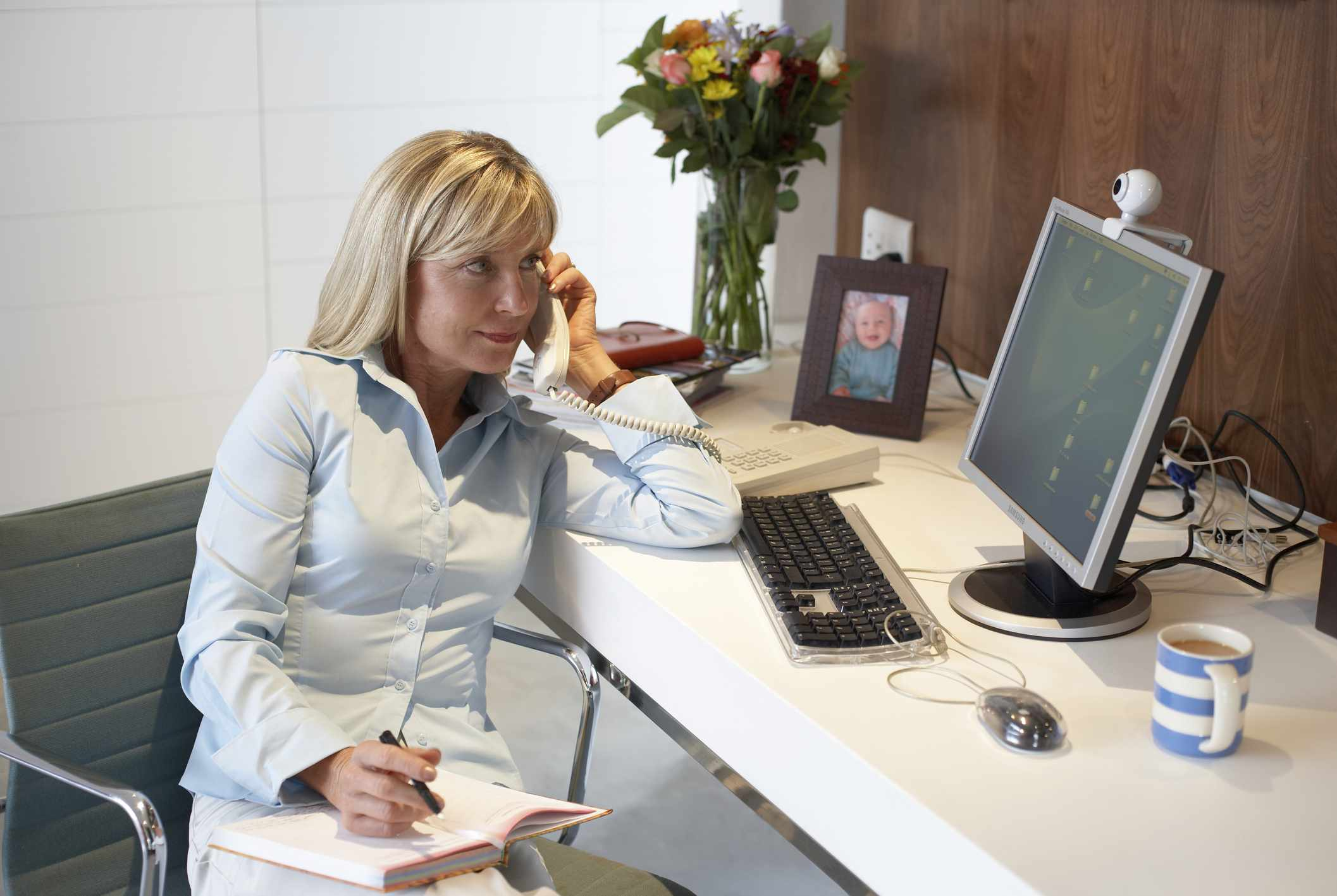 Woman working from home with computer and telephone